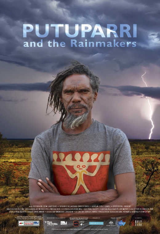 An Indigenous man stands with his arms crossed in from of a desert landscape with dark skies and a lightening bolt striking ground over his shoulder.